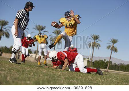 American Football-Spieler, die versuchen, Rivalität Teammitglied während der Schiedsrichter gerade auf Feld zu blockieren