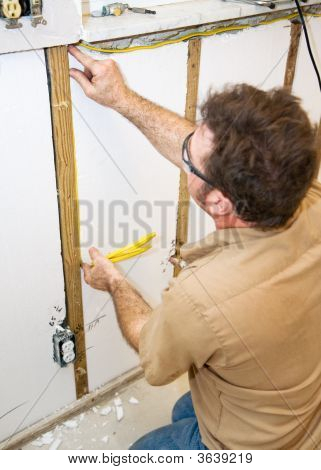 Electrician Installs Wiring In Wall