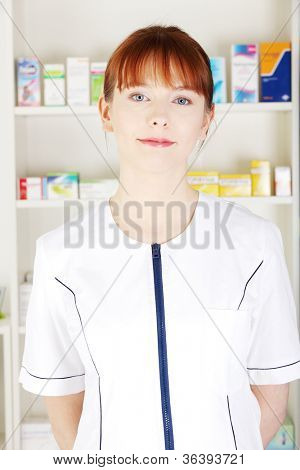 Young woman in pharmacist uniform standing and smiling in drugstore