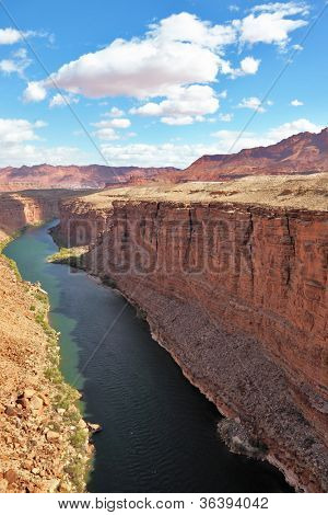 Majestic landscape. Green water of the river Colorado in abrupt coast of desert from red sandstone