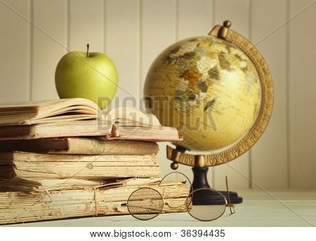 Old books with apple and globe