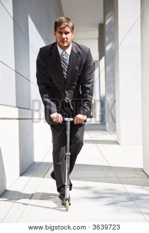 Caucasian Businessman Riding Scooter