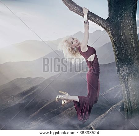 Attractive blonde lady hanging on a tree