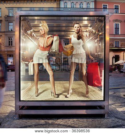 Duas mulheres compras na janela de exposição