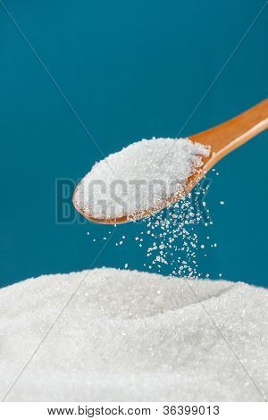 Sugar pouring from a spoon to a pile