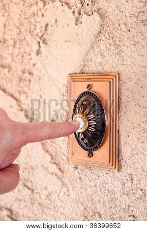 A visitor pushing a brass, antique doorbell that's mounted to a stucco wall.