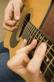 image of acoustic guitar  - shot of hands playing an acoustic guitar with a plectrum - JPG