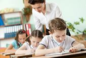 stock photo of conduction  - Teacher conducts the task performing by her pupils - JPG