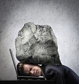 stock photo of fatigue  - Young businessman with his head squeezed between a laptop keyboard and a rock - JPG