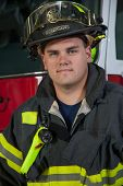 Young Handsome Firefighter standing in front fire truck close-up portrait