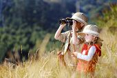 stock photo of safari hat  - Children brother and sister playing outdoors pretending to be on safari and having fun together with binoculars and hats - JPG