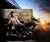 stock photo of chopper  - Sexy young fit male model on motorcycle outdoors at dawn - JPG