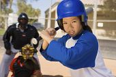 picture of umpire  - Young Asian softball player holding bat with keeper and umpire in the background - JPG