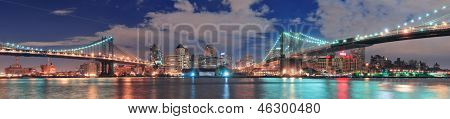 Manhattan Bridge and Brooklyn Bridge panorama over East River at night in New York City Manhattan with lights and reflections.