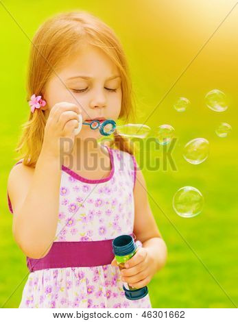 Closeup portrait of cute baby girl blowing soap bubbles outdoors, playing game on spring garden, sunny day, happy childhood concept