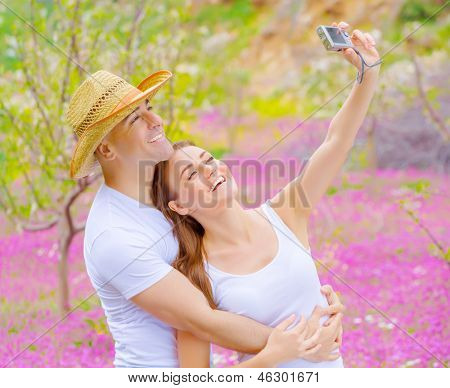 Cute cheerful couple make photo of themselves outdoors on beautiful pink floral meadow in summer garden, affection and romance concept, happy weekend
