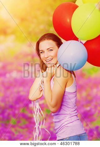 Cute cheerful female having fun with bunch of colorful balloons in spring garden, birthday celebration, happiness concept