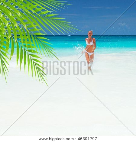 Young lady runs out of the sea, beautiful seascape, relaxation outdoors, having fun on the beach, fresh green palm tree leaves, summer vacation concept