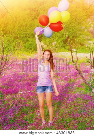 Happy young woman holding in hands many colorful balloons, having fun on purple floral field, summer time season, freedom concept