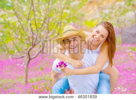 Young happy family spending time together in summer garden, handsome man carry on the hands his beautiful woman, summer vacation concept