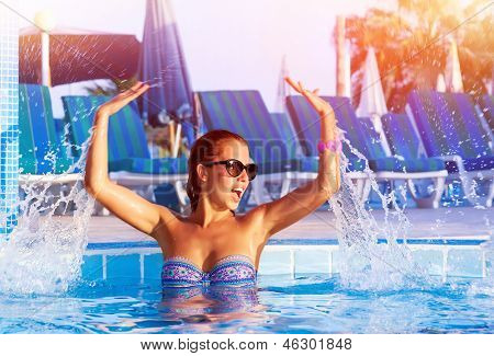 Happy pretty girl having fun in the pool, cute playful female splashing water in swimming pool, relaxation and play in poolside, summer vacation concept