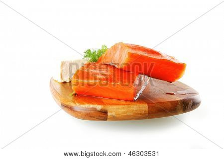 sinlge pink salmon bit on a big wooden dish with white cheese