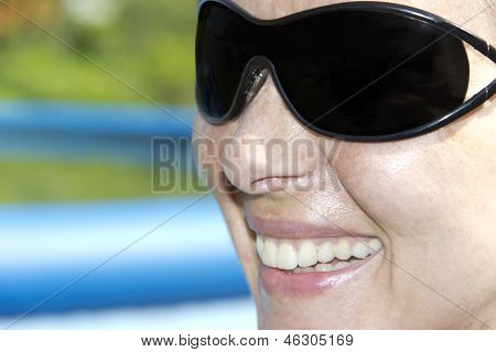 The Face Of A Smiling Woman In Sunglasses