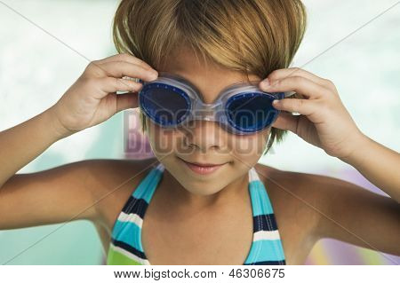 Closeup of a little blond girl adjusting goggles