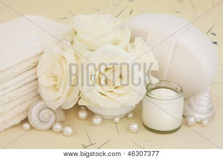 Rose flowers with bathroom accessories of moisturiser cream, pearls and shells over mottled background.