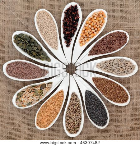 Seed food selection in white porcelain bowls over hessian background.