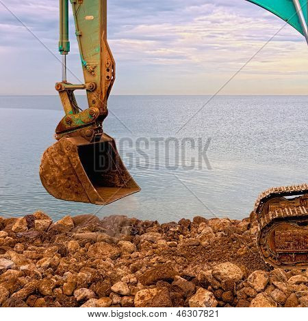 Excavating Rocks By The Sea