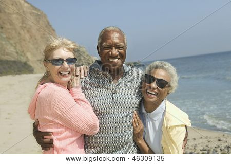 Portrait of happy multiethnic friends embracing on the beach