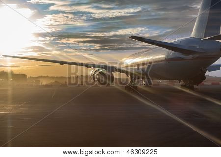 Passenger Aircraft Standing On Runway In Sunset Sunlights