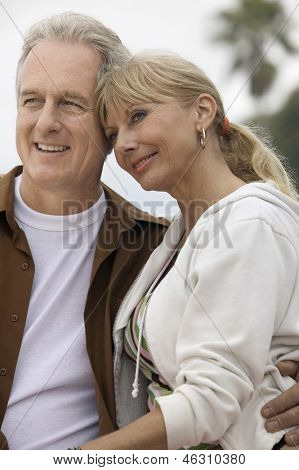 Smiling relaxed middle aged couple looking away at the beach