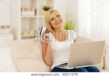 Smiling young woman using laptop and holding credit card
