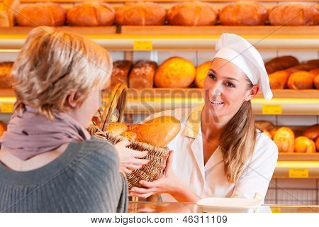 Female baker or saleswoman in her bakery with a female customer and fresh pastries or bakery products