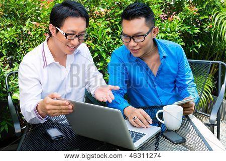 Asiatische Geschäftsleute arbeiten im freien - sie sitzen mit Laptop in einem Café und Brainstorming