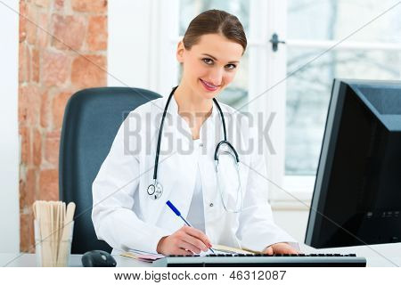 Young female doctor sitting at a desk in front of window in clinic writing a file or dossier
