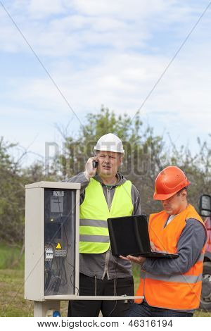 Eletricistas com PC e pasta perto de central telefônica