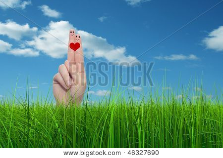 Concept or conceptual human man woman hand finger faces in love with a red heart shape painted in grass over sky background