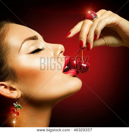 Sexy Woman Eating Cherry. Sensual Red Lips. Red Manicure, Lipstick and Ring. Desire. Sexy red Lips with Cherries isolated on Black