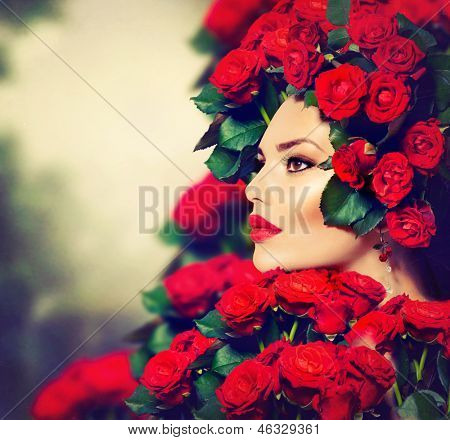 Beauty Fashion Model Girl Portrait with Red Roses Hairstyle. Red Lips and Nails. Beautiful Luxury Makeup and Hair and Manicure Vogue Style