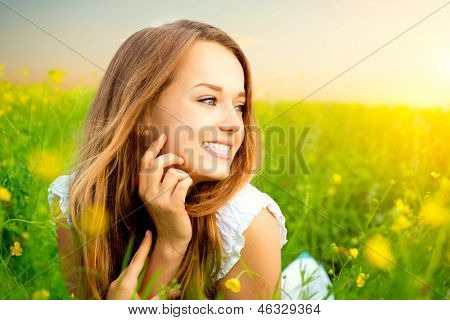 Beauty Girl in the Meadow. Beautiful Young Woman Outdoors. Enjoy Nature. Healthy Smiling Girl lying on Green Grass with wild Flowers. Laughing And Happy