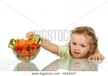 Little Girl Stealing A Vegetable From A Bowl