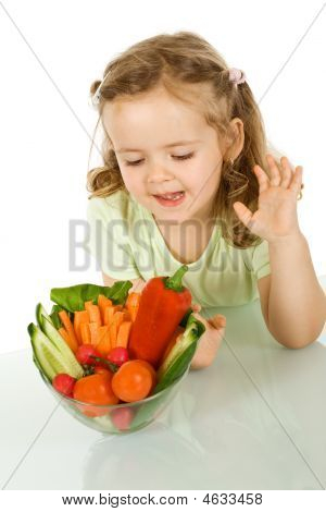 Little Girl Looking At A Bowl Of Vegetables