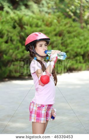 Little girl in roller skates drinking water at  park