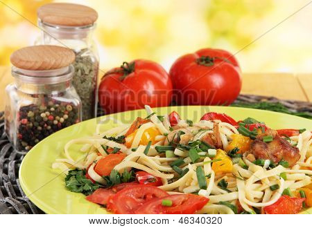 Noodles with vegetables in plates on bright background close-up