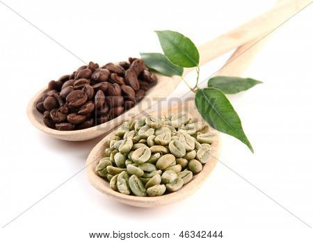 Green  and brown coffee beans in wooden spoons and leaves isolated on white