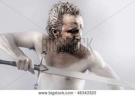 Warrior man covered in mud with sword