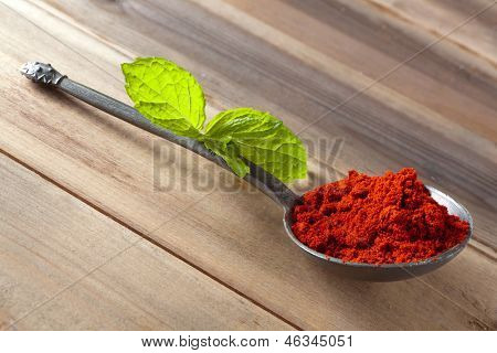 Red hot paprika powder spice in an antique pewter spoon on a wooden table